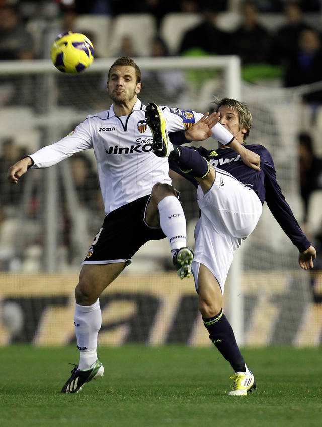 Real Madrid's Nuri Sahin of Turkey, right, duels for the ball with Valencia's Roberto Soldado, left,  during their La Liga soccer match at the Mestalla stadium in Valencia, Spain, Sunday, Jan. 20, 2013. (AP Photo/Alberto Saiz)