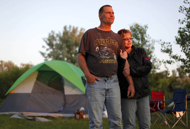 "In a June 27, 2011 photo, Galen and Teresa Schaan stand outside their family's $54 Wal-Mart tent pitched on the grounds of the Maysa Park Arena, a winter sports facility, in Minot, N.D. Schaan's family are among the thousands of people left homeless due to the flooded river that has inundated more than 4,000 houses in North Dakota's fourth-biggest city. ""We wanted to go camping all summer but not like this,"" said Galen Schaan, 48, a burly soft-spoken man who works as a roughneck in North Dakota's oil patch. (AP Photo/Charles Rex Arbogast)"