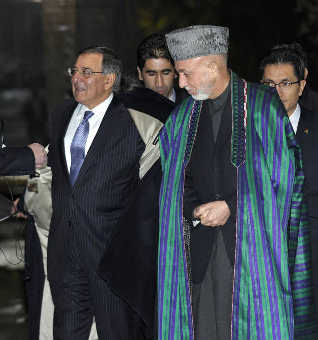 U.S. Defense Secretary Leon Panetta, left, takes off his coat as he and Afghanistan President Hamid Karzai arrive for a joint news conference at the Presidential Palace in Kabul, Afghanistan, Thursday, Dec. 13, 2012. (AP Photo/Susan Walsh, Pool)