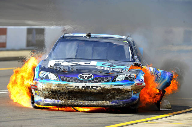 Denny Hamlin drives down pit road with his car engulfed in fire during Sunday's race at Michigan International Speedway. AP Photo
