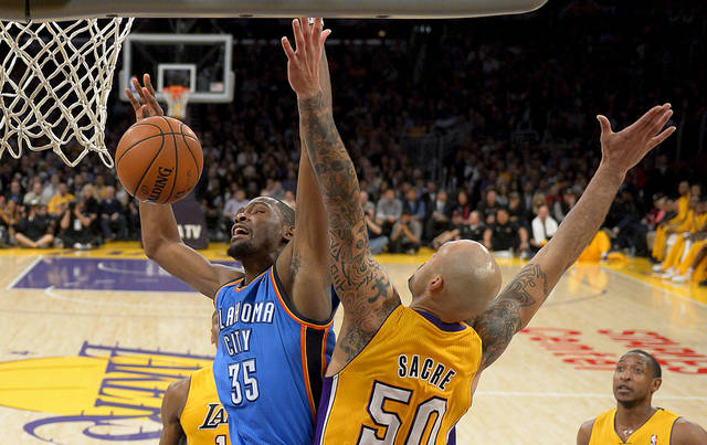 Oklahoma City Thunder forward Kevin Durant, left, battles Los Angeles Lakers center Robert Sacre for a rebound during the first half of their NBA basketball game, Friday, Jan. 11, 2013, in Los Angeles. (AP Photo/Mark J. Terrill)