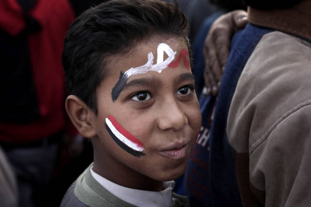 "A boy with the colors of the Egyptian flag and Arabic that reads, ""Egypt,"" painted on his face attends a demonstration in Tahrir Square, Cairo, Egypt, Friday, Nov. 30, 2012. Liberal and secular parties held major protests against Egyptian President Mohammed Morsi's latest decrees granting himself almost complete powers. (AP Photo/Nariman El-Mofty)"