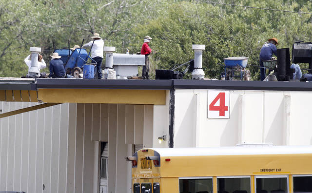 Workers make repairs to a hail damaged roof recently at the Oklahoma City Public Schools service center in northeast Oklahoma City. Hailstorms in 2010 and 2012 damaged dozens of buildings throughout the school district. Photo by Steve Gooch, The Oklahoman <strong>Steve Gooch</strong>