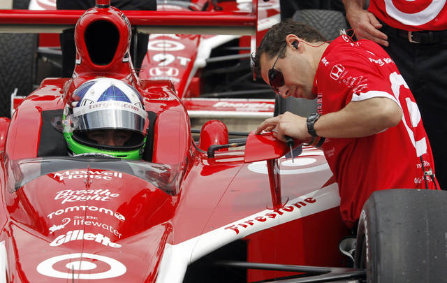 In this May 14, 2011 photo, IndyCar driver IndyCar driver Dario Franchitti, of Scotland, has his mirror adjusted by a crewman as he sits in the car during practice for the Indianapolis 500 at the Indianapolis Motor Speedway in Indianapolis. The Speedway started as a testing ground for the automotive industry and a century later it still is perfecting items such as the rear-view mirror, safer tires and other high-tech advancements.(AP Photo/Darron Cummings)