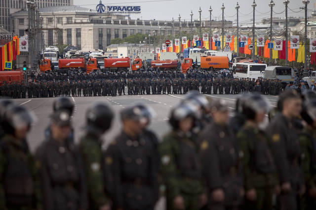 """Russian Police officers stand facing an opposition protest to block the road in the center of Moscow during a rally, Sunday, May 6, 2012. Thousands of protesters are gathering at a Moscow square for a march on the eve of Vladimir Putin's inauguration as president.The protest has been boldly billed by opposition leaders as the """"March of a Million,"""" but the early turnout indicates the numbers won't be anywhere close to that. About 5,000 had gathered an hour before the planned start of the Sunday march.(AP Photo/Alexander Zemlianichenko)"""