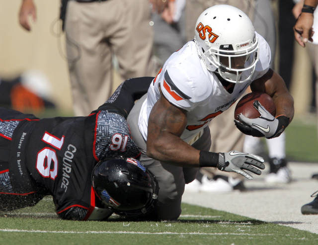 Oklahoma State's Jeremy Smith (31) is tackled by Texas Tech's Cody Davis (16)during a college football game between Texas Tech University (TTU) and Oklahoma State University (OSU) at Jones AT&T Stadium in Lubbock, Texas, Saturday, Nov. 12, 2011.  Photo by Sarah Phipps, The Oklahoman  ORG XMIT: KOD