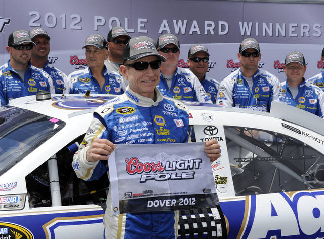 Driver Mark Martin poses with the flag after he won the pole during qualifying for Sunday's NASCAR Sprint Cup Series auto race, Saturday, June 2, 2012, in Dover, Del. (AP Photo/Nick Wass)
