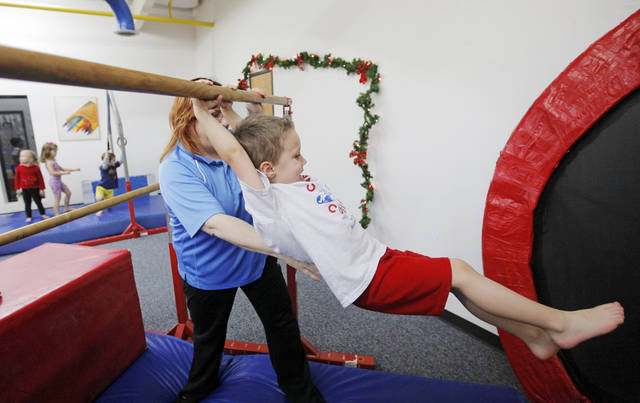 CHILD / CHILDREN / KIDS: Preschool director Teresa Rhame helps Evan Borchardt, 4, swing from a bar during Conner's Cubbies, a class for preschoolers at Bart Conner Gymnastics Academy in Norman, Okla., Wednesday, Dec. 14, 2011. Photo by Nate Billings, The Oklahoman