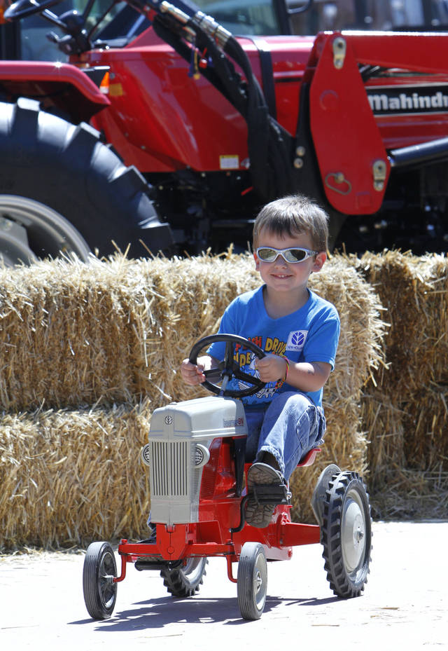 Logan Cravens, 3, Edmond, pedals a tractor through a hay bale track at the Oklahoma State Fair, Tuesday, September 18, 2012. Photo By David McDaniel/The Oklahoman