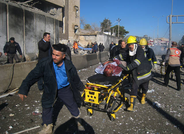 Iraqi firefighters evacuate a victim at the scene of a bomb attack in Kirkuk, 180 miles (290 kilometers) north of Baghdad, Iraq, Sunday, Feb. 3, 2013. A suicide car bomber joined by other suicide attackers on foot assaulted a provincial police headquarters in a disputed northern Iraqi city killing and wounding scores of people, police said. (AP Photo/Emad Matti)