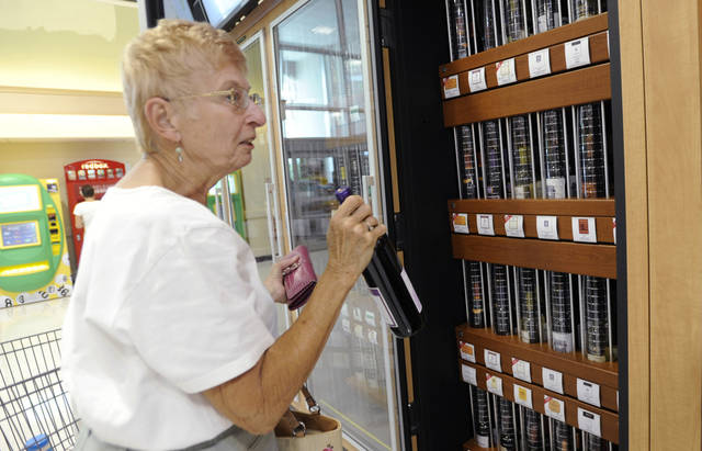 In this June 25, 2010 photo, Jacqueline Love purchases her first bottle of wine from the Pennsylvania Liquor Control Board's self-serve wine kiosk at a Giant food store, in Harrisburg, Pa. (AP Photo/Bradley C Bower)