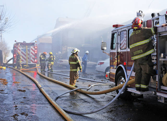 Firefighters work Wednesday to put out a fire at the Eden Cove Apartments in Midwest City.  Photo by Garett Fisbeck, For The Oklahoman