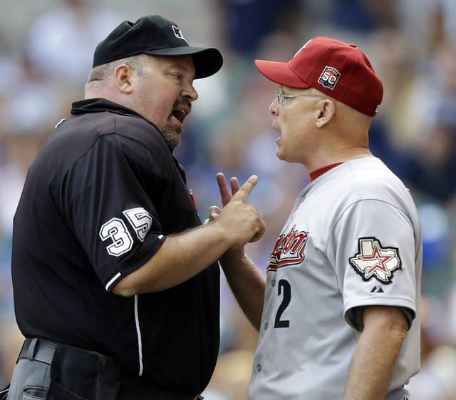 Houston Astros manager Brad Mills, right, argues with home plate umpire Wally Bell during the eighth inning of a baseball game against the Milwaukee Brewers, Wednesday, Aug. 1, 2012, in Milwaukee. (AP Photo/Jeffrey Phelps)