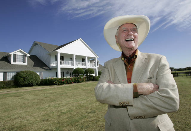 "FILE - In this Oct. 9, 2008, file photo, the late Actor Larry Hagman poses in front of the  Southfork Ranch mansion made famous in the television show, ""Dallas"",  in Parker, Texas. Tourists have been flocking to Southfork Ranch since the early years of the classic series, which ran from 1978 to 1991. And a new �Dallas� starting its second season on TNT on Monday and the recent death of the show's star, Larry Hagman, who legendarily played conniving Texas oilman J.R. Ewing, have also spurred fans to visit. (AP Photo/Tony Gutierrez, file)"