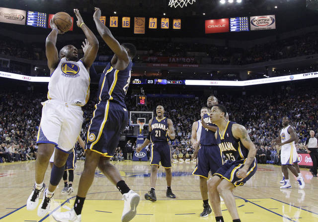 Golden State Warriors' Carl Landry (7) shoots next to Indiana Pacers' Ian Mahinmi, second from left, during the first half of an NBA basketball game in Oakland, Calif., Saturday, Dec. 1, 2012. (AP Photo/Marcio Jose Sanchez)