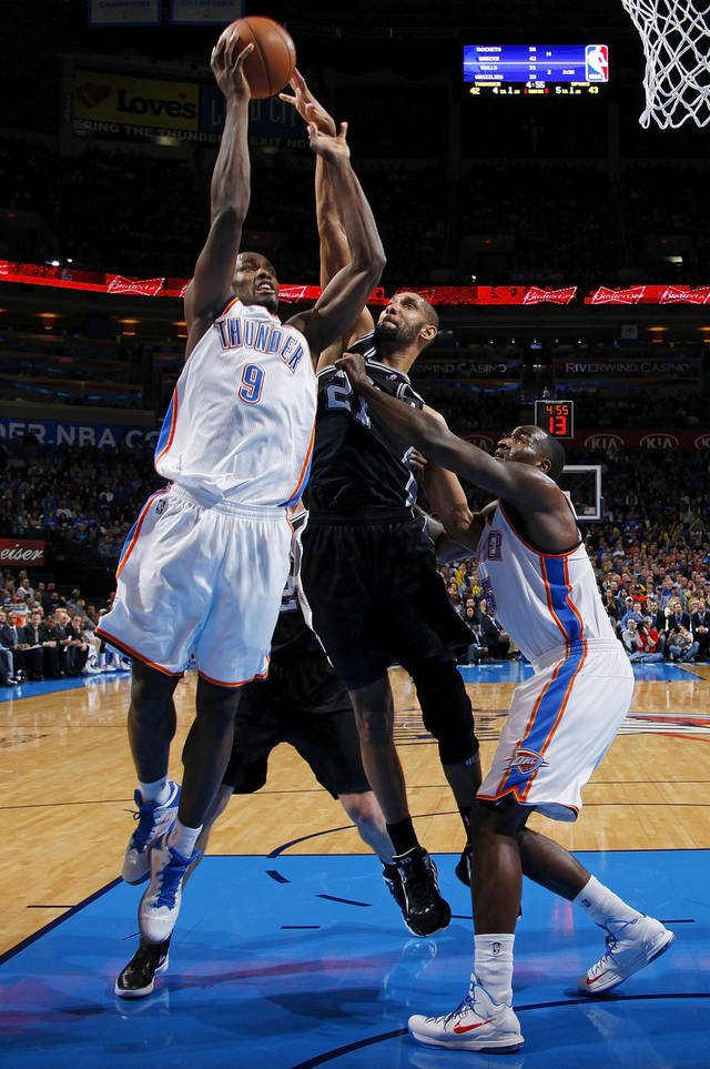 Oklahoma City's Serge Ibaka (9) shoots as San Antonio's Tim Duncan (21) defends next to Oklahoma City's Kendrick Perkins (5) during an NBA basketball game between the Oklahoma City Thunder and the San Antonio Spurs in Oklahoma City Monday, Dec. 17, 2012. Oklahoma City won, 107-93. Photo by Nate Billings, The Oklahoman