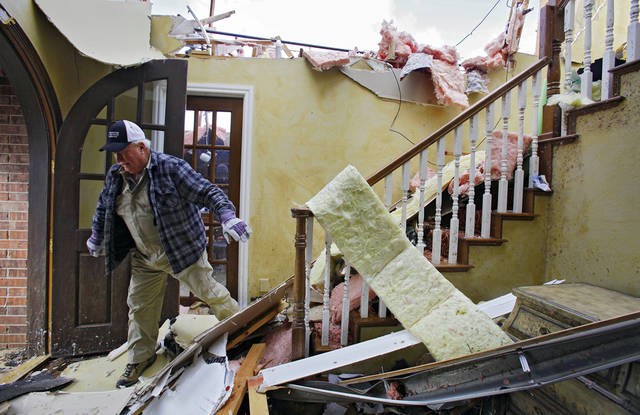 Bob Haslam navigates his way down stairs as he helps remove items from his daughter's home that was heavily damaged in the Oak Tree addition on Wednesday, Feb. 11, 2009, after a tornado hit the area on Tuesday in Edmond, Okla.  PHOTO BY CHRIS LANDSBERGER, THE OKLAHOMAN