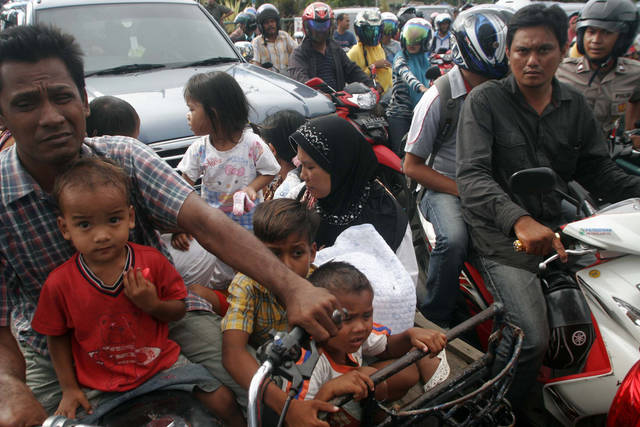 FILE- In this April 11, 2012 file photo, people are stuck in a traffic jam as they evacuate to higher ground after a strong earthquake was felt in Banda Aceh, Aceh province, Sumatra island, Indonesia. Residents living in tsunami-scarred Aceh province should prepare themselves for a possible repeat of the 2004 disaster, a leading seismologist said, noting historical data indicates tremendous stresses building up along the explosive fault could unleash again anytime within the next half century. (AP Photo/Heri Juanda, File)
