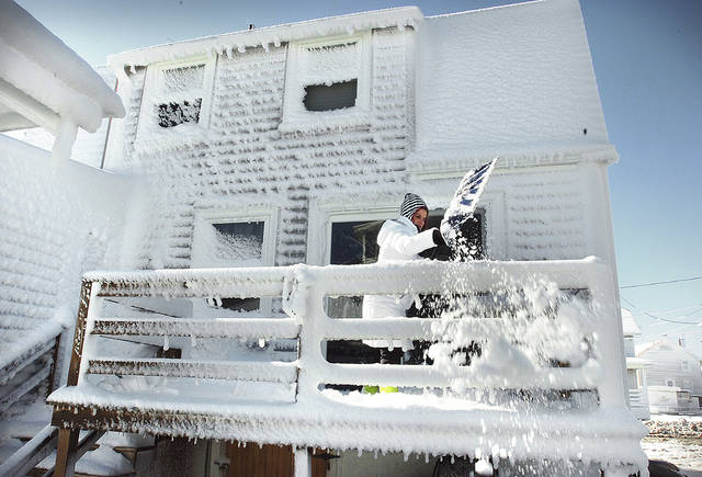 Kris Kachline clears the back deck of her snow-encrusted home in the Windmill Point neighborhood of Hull, Mass., Sunday, Feb. 10, 2013, after more than two feet of snow blanketed the region from a storm that ended Saturday.  (AP Photo/The Patriot Ledger, Gary Higgins)  BOSTON OUT