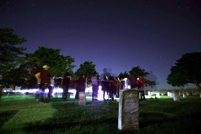 In this long exposure image a crowd listens to paranormal stories at the post cemetery during a guided ghost tour by lantern light around Fort Reno in El Reno on Saturday, Sept. 21, 2013. Photo by Bryan Terry, The Oklahoman