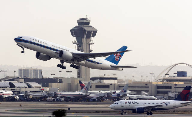 File-This Monday, April 22, 2013, file photo shows a China Southern Cargo jet taking off at LAX International airport in Los Angeles. The Los Angeles City Council voted to approve a long-debated, multibillion-dollar plan to expand and modernize LAX, despite intense opposition from community groups who claim the project would increase traffic congestion and air pollution. (AP Photo/Damian Dovarganes,File)