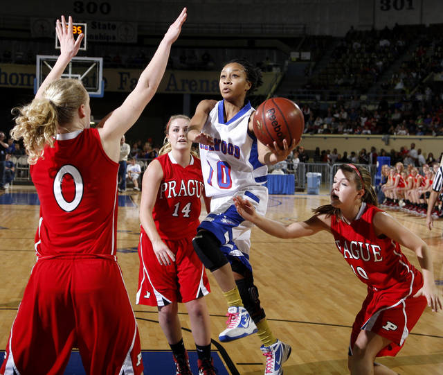 Millwood&#039;s Teanna Reid goes to the basket between Prague&#039;s Whitney Stotler, left, Alex Tilton, and Ellie Schultz, at right, during the Class 3A girls high school state basketball championship game at State Fair Arena in Oklahoma City, Saturday, March 10, 2012. Photo by Bryan Terry, The Oklahoman