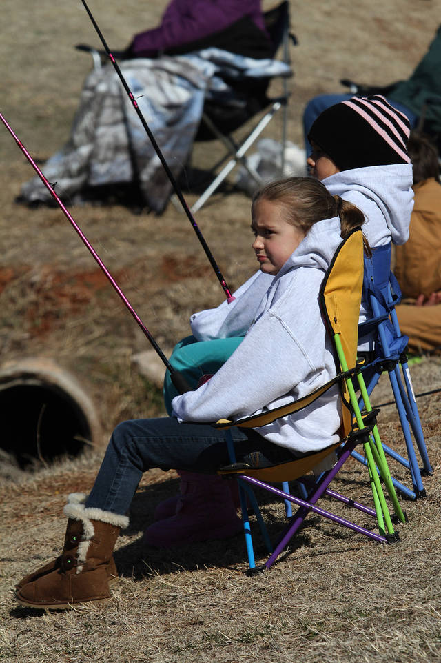 Jaycee McKee, front, and her friend Victoria Hughes, both 7, watch their lines during the Trout Fish Out Saturday, March 2, 2013,  morning at the Dale Robertson Activity Center pond in Yukon. PHOTO BY HUGH SCOTT FOR THE OKLAHOMAN