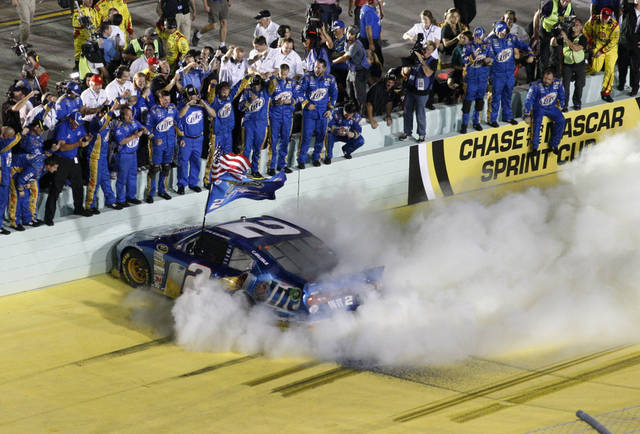 Brad Keselowski celebrates with his crew after winning the NASCAR Sprint Cup Series championship following an auto race at Homestead-Miami Speedway, Sunday, Nov. 18, 2012, in Homestead, Fla. Keselowski clinched the Sprint Cup title after fellow title contender Jimmie Johnson pulled out of the season finale because of a parts failure. Jeff Gordon won the race. (AP Photo/Wilfredo Lee)