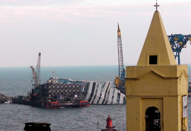 FILE - This Jan. 11, 2013 file photo shows the cruise ship Costa Concordia leaning on its side, near the shore of the Tuscan island of Giglio, Italy.  Thirty-two people died when the ship ran aground on Jan. 13, 2012. Cruise watchers looking back at the industry's past year say the Concordia disaster affected everything from prices to safety drills to first-time cruisers, but bookings appear to be picking up as the 2013 cruise booking season gets under way. The first three months of each year are known as �wave season,�a period when many cruisers book trips as they plan ahead for summer vacations.  (AP Photo/Paolo Santalucia, file)
