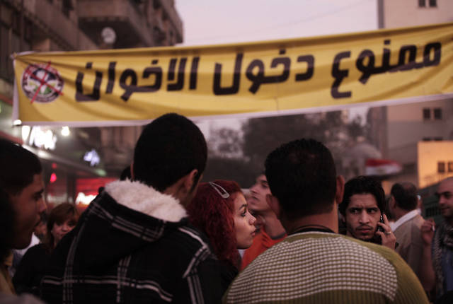 "Egyptians gather in front of a banner in Arabic that reads, ""members of the Muslim Brotherhood are not allowed,"" during a demonstration in Tahrir Square, Cairo, Egypt, Friday, Nov. 30, 2012. Liberal and secular parties held major protests against Egyptian President Mohammed Morsi's latest decrees granting himself almost complete powers.(AP Photo/Nariman El-Mofty)"