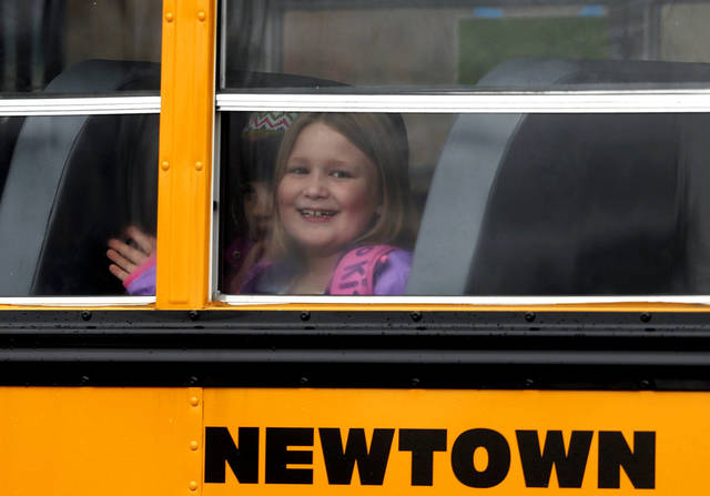 A young girl waves as her school bus pulls into Hawley School, Tuesday, Dec. 18, 2012, in Newtown, Conn.  Classes resume Tuesday for Newtown schools except those at Sandy Hook. Buses ferrying students to schools were festooned with large green and white ribbons on the front grills, the colors of Sandy Hook. At Newtown High School, students in sweatshirts and jackets, many wearing headphones, betrayed mixed emotions.  Adam Lanza walked into Sandy Hook Elementary School in Newtown,  Friday and opened fire, killing 26 people, including 20 children, before killing himself.(AP Photo/Jason DeCrow) ORG XMIT: CTJD106