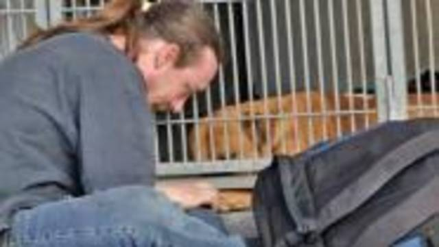 Man sobbing at animal shelter. After being jailed briefly and his dog Buzz Lightyear impounded he couldn't afford the $400 to get his pet back.
