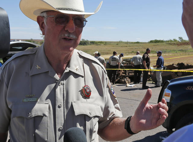 Custer County Sheriff Bruce Peoples answers questions as investigators work on two cars found a day earlier in Foss Lake, in Foss, Okla., Wednesday, Sept. 18, 2013.  The Oklahoma State Medical Examiner's Office says authorities have recovered skeletal remains of multiple bodies in the Oklahoma lake where the decades-old cars were recovered. (AP Photo/Sue Ogrocki)