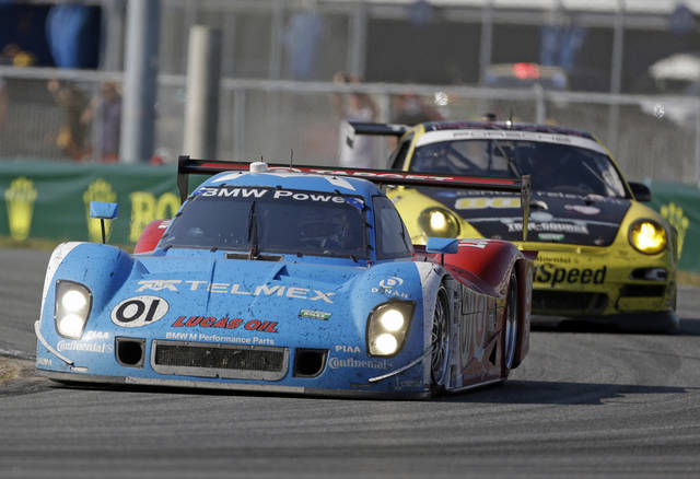 Memo Rojas, of Mexico, in the Ganassi Racing BMW Riley (01) passes a GT series car in a horseshoe turn during the Grand-Am Series Rolex 24 hour auto race at Daytona International Speedway, Sunday, Jan. 27, 2013, in Daytona Beach, Fla. (AP Photo/John Raoux)