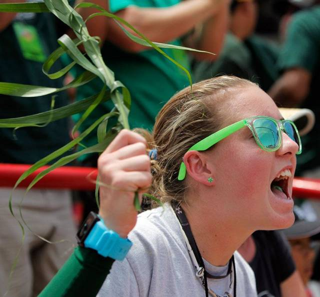 Demi Coolen, 16, waves a ti leaf for good luck  as she cheers for Hawaii during a softball game between Hawaii and University of Missouri in the first session of the Women's College World Series at ASA Hall of Fame Stadium in Oklahoma City, Thursday, June 3, 2010.  Coolen is the daughter of Hawaii head coach Bob Coolen. Hawaii won, 3-2. Photo by Nate Billings, The Oklahoman