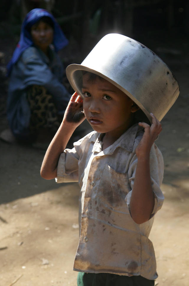 In this photo taken on Nov. 10, 2012, a Muslim boy walks with a empty pan at Sin Thet Maw relief camp in Pauk Taw township, Rakhine state, western Myanmar. Stranded beside their decrepit flotilla of wooden boats, on a muddy beach far from home, the Muslim refugees tell story after terrifying story of their exodus from a once-peaceful town on Myanmar's western coast. The Oct. 24 exodus was part of a wave of violence that has shaken western Myanmar twice in the last six months.  (AP Photo/Khin Maung Win)