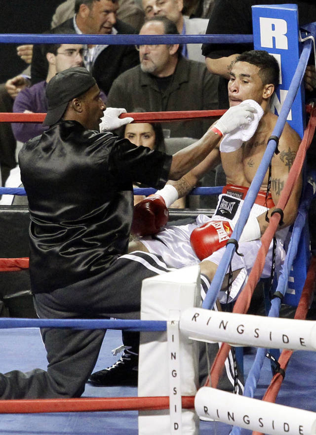 In this photo taken April 28, 2012, boxer Martin Tucker, right, from Toledo,Ohio is tended to during a boxing match against Devaris Crayton at the Huntington Center in Toledo, Ohio. The FBI said it obtained a swab used to stop Tucker's bleeding in his April fight and found that his DNA matched the DNA on evidence from a 2009 robbery at Monroe County Community Credit Union in Temperance, near the Michigan-Ohio border. Tucker was arrested this week and ordered held without bond on Wednesday, July 18, 2012. (AP Photo/The Blade, Amy E. Voigt) MANDATORY CREDIT; MAGS OUT; NO SALES; TV OUT; SENTINEL-TRIBUNE OUT; MONROE EVENING NEWS OUT; TOLEDO FREE PRESS OUT