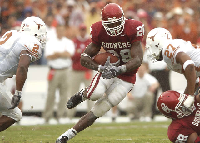 DALLAS, TEXAS, SATURDAY, OCTOBER 9, 2004. OKLAHOMA SOONERS VS TEXAS AT THE COTTON BOWL IN DALLAS, TEXAS. Oklahoma Sooners runningback Adrian Peterson (28) rushes through the Texas defense against Texas' Aaron Harris (2) and Michael Griffin (27) in the first half Saturday in Dallas. Nate Billings/The Oklahoman