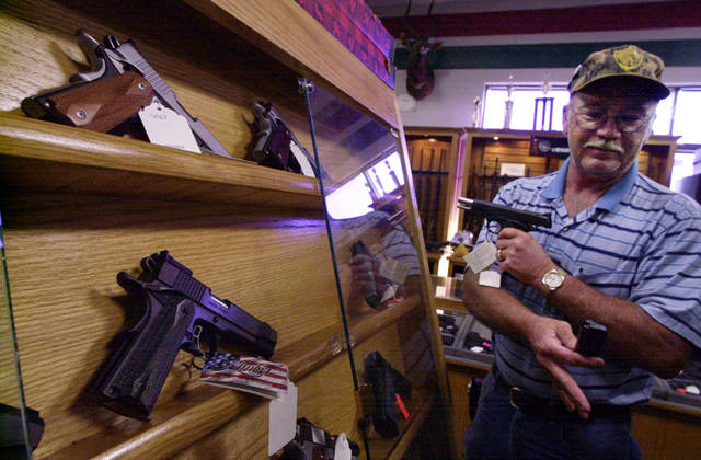 In this file photo, Martin Adams of Moore looks over a gun at H&H Gun Range. <strong>BRYAN TERRY</strong>