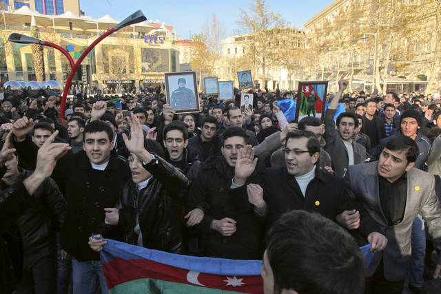 Demonstrators carry portraits of Jeyhun Gubabov, who authorities say died of heart failure during a rally in downtown Baku, Azerbaijan, Saturday Jan. 12, 2012. Several hundred people have rallied in the center of Azerbaijan's capital in a social media-organized gathering in protest at the death earlier this month of the military conscript. Gubabovi's mother says he was the victim of physical mistreatment.(AP Photo/Turxan Kerimli)