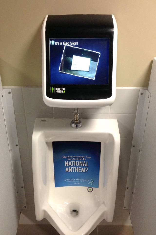In this Tuesday, March 26, 2013 photo provided by the Lehigh Valley IronPigs minor league baseball team,  a urinal gaming system is shown in a men's restroom at Coca-Cola Park in Allentown, Pa.  It consists of a video display mounted above each urinal. When a fan approaches, the video console will sense his presence and switch into gaming mode. The guy aims left or right to control the play on the screen. The team said Tuesday that Coca-Cola Park will be the first sports venue in the world to feature the gaming system. It'll be ready by opening day next week. (AP Photo/Lehigh Valley IronPigs)