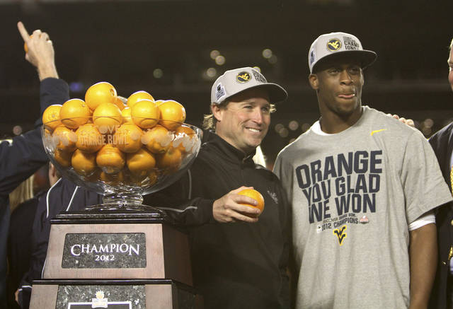 West Virginia coach Dana Holgorsen, left, and quarterback Geno Smith pose for photos after the Orange Bowl NCAA college football game in MIami, Wednesday, Jan. 4, 2012. West Virginia defeated Clemson 70-33.  (AP Photo/J Pat Carter) ORG XMIT: SLS133