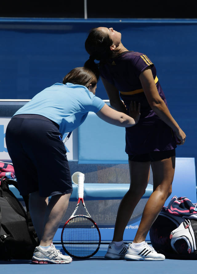 Jamie Hampton of the US gets treatment during her third round match against Victoria Azarenka of Belarus at the Australian Open tennis championship in Melbourne, Australia, Saturday, Jan. 19, 2013. (AP Photo/Andy Wong)