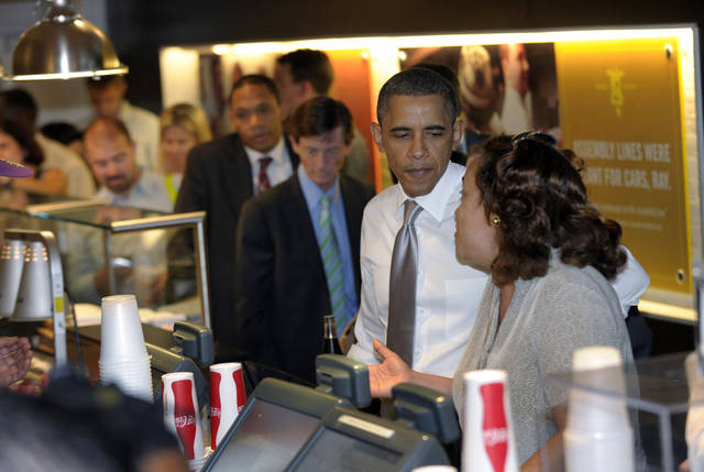 FILE - In this Aug. 3, 2011 file photo, President Barack Obama waits to order lunch at Good Stuff Eatery in Washington. Call it the Obama effect: a presidential visit can be good advertising for the restaurants and businesses. Interest in where and what Obama and his family does can be explained with one word: authenticity. (AP Photo/Susan Walsh, File)