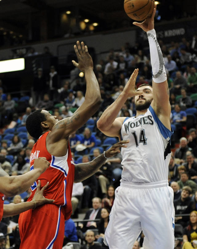 Minnesota Timberwolves' Nikola Pekovic, right, of Montenegro, hoots over Los Angeles Clippers' DeAndre Jordan during the first half of an NBA basketball game on Thursday, Jan. 17, 2013, in Minneapolis. (AP Photo/Jim Mone)