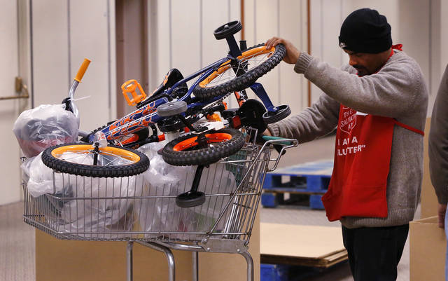A volunteer places a bicycle with other bags of toys in a shopping cart before it is given to a client. The Salvation Army and Feed the Children teamed to distribute bicycles and toys for children,  and handed out boxes of food for families at their annual distribution event Wednesday, Dec. 19, 2012. Salvation Army officials said 100 volunteers helped make the event go smoothly. The volunteers loaded bags of toys and bikes into vehicles of clients who had been pre-approved for assistance.  Many of the gifts were provided through the Salvation Army&#039;s Angel Tree program   Photo by Jim Beckel, The Oklahoman