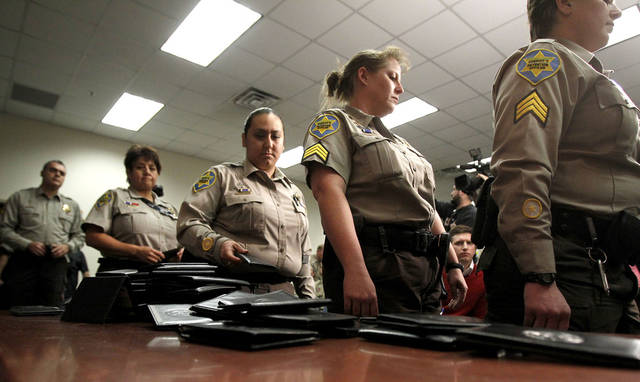 Maricopa County Sheriff's Office immigration jail officers, who lost their federal power to check whether inmates are in the county illegally, turn in their credentials after federal officials pulled the Sheriff's office immigration enforcement powers Wednesday, Dec. 21, 2011, in Phoenix. The U.S. Department of Homeland Security stripped Sheriff Joe Arpaio's jail officers of their federal powers after federal authorities accused the sheriff's office last week of a wide range of civil rights violations.(AP Photo/Ross D. Franklin)