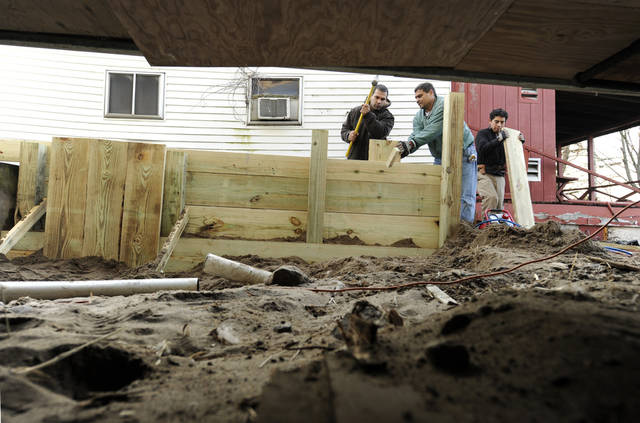 In this Tuesday, Dec. 4, 2012 photo, builders Reginaldo Ferreira, left, Liudmil Petrov, center, and Carlos Martinez of Russe Builders construct a wall to protect a beachfront home in Fairfield, Conn.  The national economy is expected to absorb the blow from Sandy with little long-term damage, but in the short term, at least, Sandy is introducing dramatic booms and busts across the Northeast. The effects vary widely across industries, bringing banner years for some while pushing others toward economic ruin. (AP Photo/Jessica Hill)
