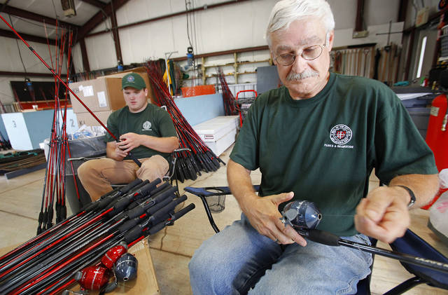 Dylan Chipera (left) and Bob Martin assemble rods and reels for the parks department and Police Athletic League fishing program. Photo by David McDaniel, The Oklahoman