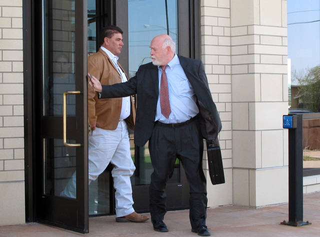 "Chippewa Cree tribal leader John ""Chance"" Houle, left, walks out of U.S. District Court in Great Falls, Mont., after being arraigned on Tuesday, May 7, 2013. Houle and four others are accused of diverting federal stimulus funds. The Chippewa Cree Tribe received $33 million in federal funding between 2009 and 2010 for construction of a $361 million pipeline to supply fresh drinking water for the Rocky Boy's Indian Reservation and surrounding counties in northern Montana. Most of that $33 million came from the 2009 American Recover and Reinvestment act, also known as the stimulus. (AP Photo/Matt Volz)"